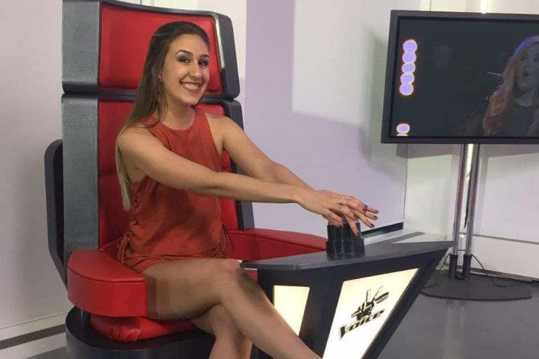 Sofia Grimsgard sitting on a red chair pressing a large button in a mock set up for The Voice television show